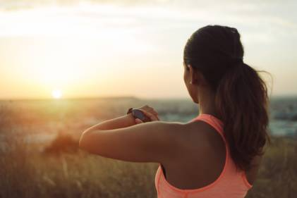 Woman checking workout goals on smart watch looking towards the sunset.