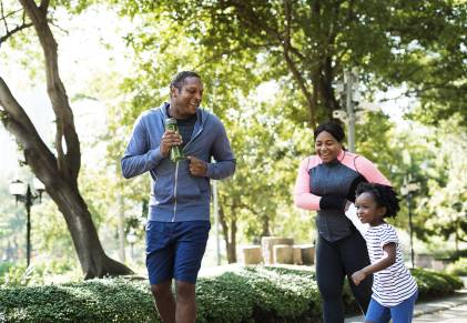 Family enjoying outdoor activity and jogging through a park.