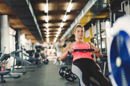 A young woman working out on an indoor rowing machine