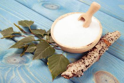Birch sugar on blue wooden background.