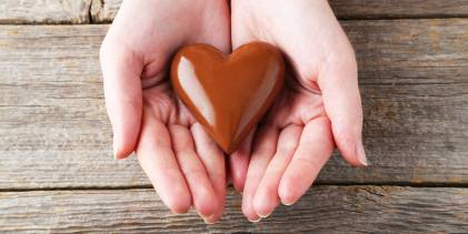 person holds heart chocolate