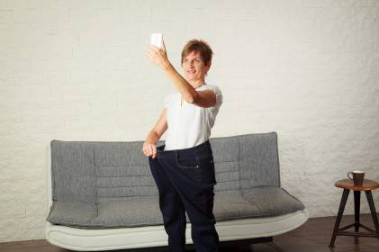 A middle-aged woman taking a selfie in pants that are too big now