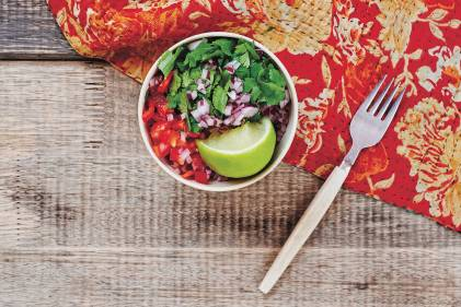 Top view of Fresh Salsa in a white bowl. A wooden table in the background with a red napkin and fork.