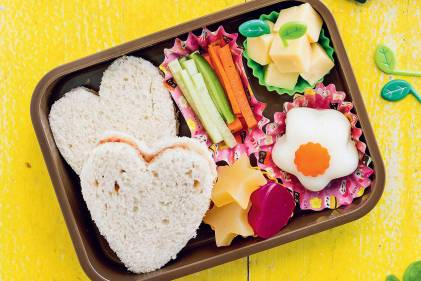 A bento box with heart-shaped sandwiches, homemade fruit snacks, cubed cheese and veggie sticks.