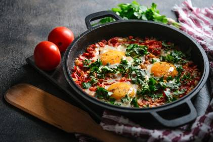 Baked Eggs with Tomatoes, Red Bell Pepper & Garlic in a iron pan on a dark background.