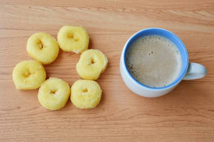 Miniature donuts next to a cup of coffee