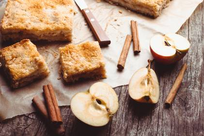 Apple cake with halved apples and cinnamon sticks on a rustic wooden table.