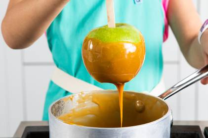 A woman dipping a Granny Smith apple in a pot of caramel to make caramel apples.