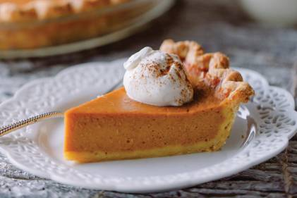 a slice of pumpkin pie with a dollop of whipped cream