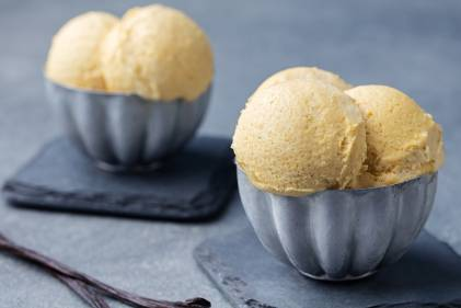 Homemade French Vanilla Ice Cream scooped into two blue bowls.