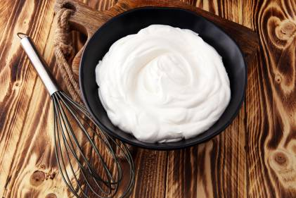 Homemade Whipped Cream in a black bowl with a whisk on a wooden table.