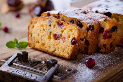 Homemade Pumpkin Cranberry Bread on a cutting board dusted with powdered sugar.