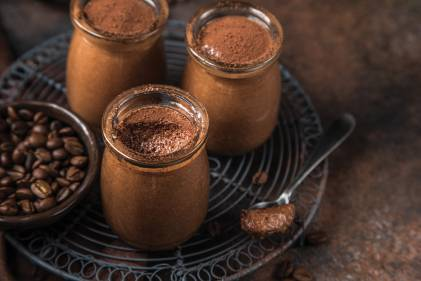 Chocolate mousse in clear glass jars, next to a small dish of coffee beans on a wire metal trivet.