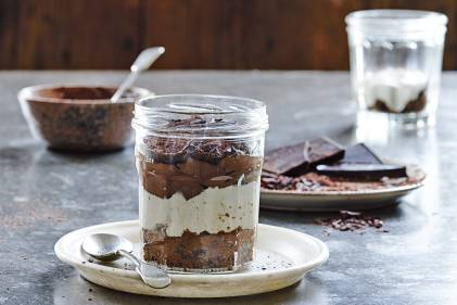 Tiramisu in a clear jar on a white plate with spoon.