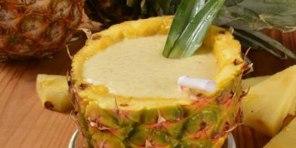 a smoothie served in a pineapple shell