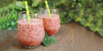 Two watermelon raspberry smoothies on wooden table.