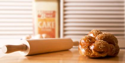 Challah bread and a rolling pin on a wooden table.