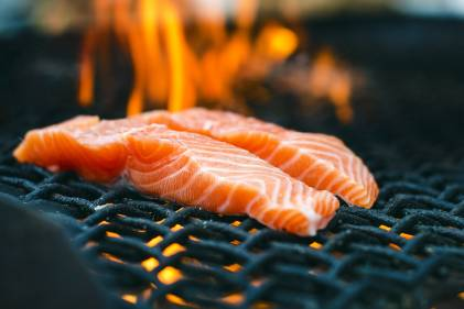 gorgeous salmon on a flaming charcoal grill