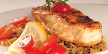 white fish filet over rice with citrus and tomatoes