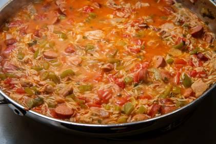Jambalaya simmering in a pan.