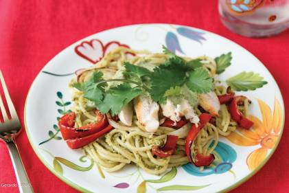 Roasted Poblano Creamy Spaghetti with Grilled Chicken, Onions, & Peppers on a colorful plate with a red tablecloth background.