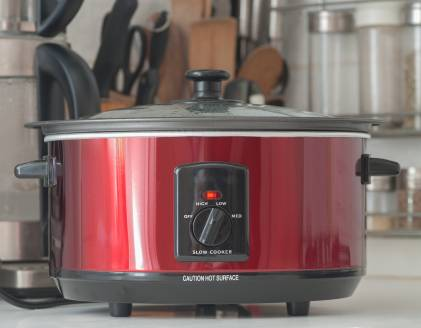 A slow cooker in use on a kitchen counter top.