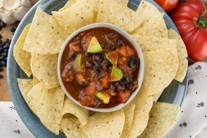 a bowl of chunky salsa surrounded by tortilla chips