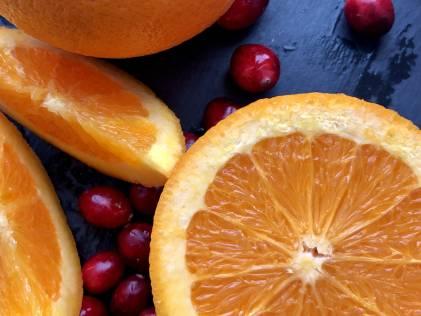 Cranberries and sliced oranges on a dark blue background.
