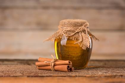 A jar of honey and cinnamon on a wooden background.