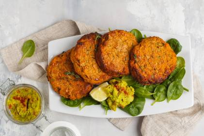 Sweet Potato and Mustard Turkey Burgers on a white platter on a bed of spinach greens.