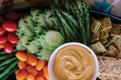 Sweet Potato Cashew Dip on a platter with veggies and crackers.