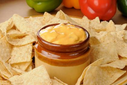 A dip with veggies surrounded by tortilla chips