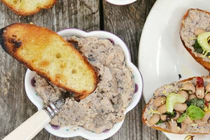 a plate of bean crostini on toasted baguette slices with parmesan over arugula