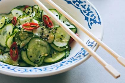 Chopsticks resting on a bowl of Thai cucumber salad