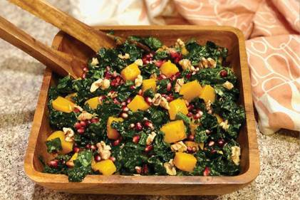 Kale, Butternut Squash, & Pomegranate Salad in a wooden salad bowl with wooden salad utensils.
