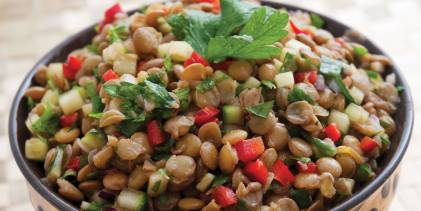a bowl of lentils and veggies with garnish