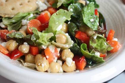 a tossed salad with greens and beans