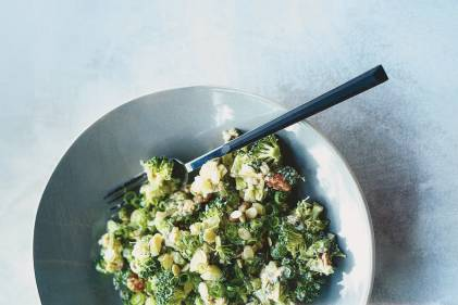 Raw Broccoli Salad in a light blue ceramic bowl on a light gray blue background.