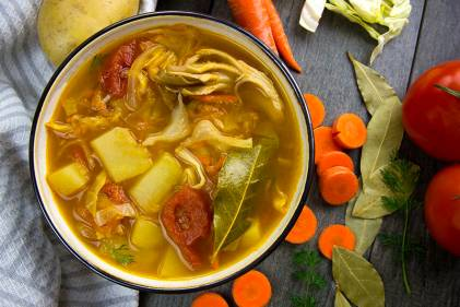 a hot bowl of soup with cabbage, potatoes, and other vegetables