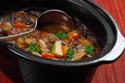 A pot full of hearty beef stew with carrots and potatoes.