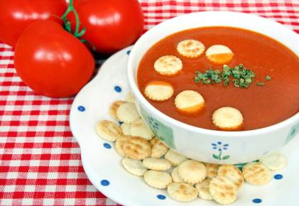 Delicious tomato soup with chives and oyster crackers.