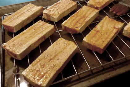 slices of tofu on the grill with a little oil