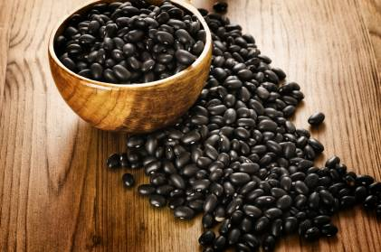Black beans in a wooden bowl placed on a wooden table.