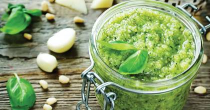 A canning jar of fresh basil pesto with garlic and cheese