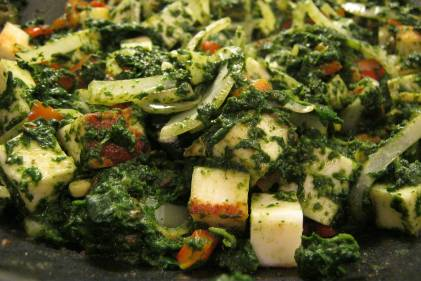 a pan of spinach and cooking cheese