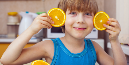 A young boy with orange slices