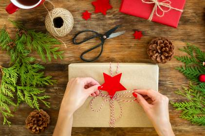 A woman tying a string bow on a gift wrapped in brown craft paper.