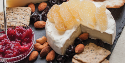 A cheese plate set with an assortment of nuts, jellies, and crackers