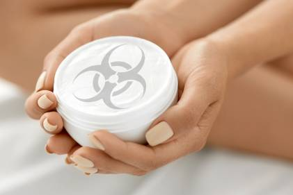 A woman holding a jar of skin cream with a biohazard symbol