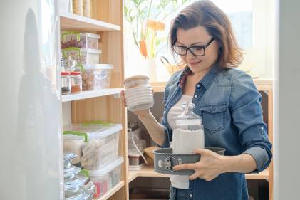 Woman selecting food from her organized kitchen pantry.